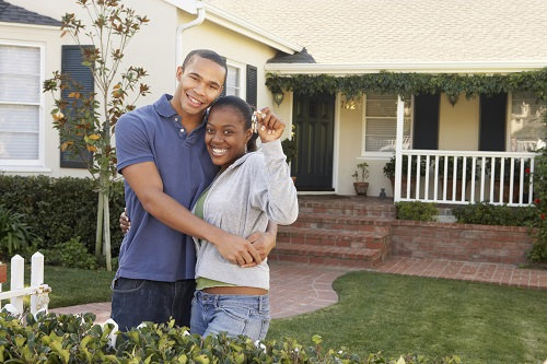 first time homebuyers holding keys in front of new home